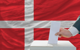 man putting ballot in a box during elections in denmark in fornt of flag